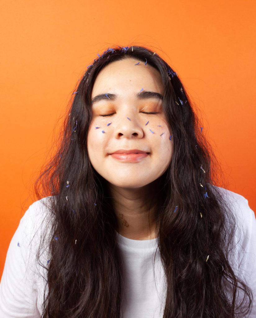 Femme asiatique avec des extraits de plantes sur son visage